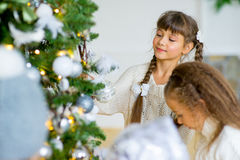 Two girls decorate the Christmas tree Stock Image