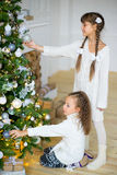 Two girls decorate the Christmas tree Stock Photography