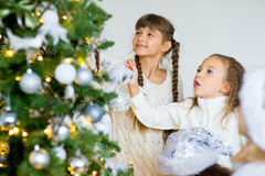 Two girls decorate the Christmas tree Royalty Free Stock Images
