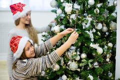 Two girls decorate the Christmas tree Royalty Free Stock Photo