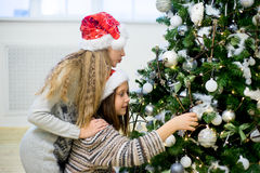 Two girls decorate the Christmas tree Royalty Free Stock Photography
