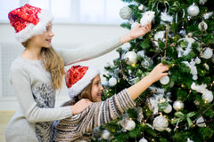 Two girls decorate the Christmas tree Royalty Free Stock Image