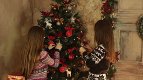 Two girls decorate Christmas tree. Two girls something discuss and decorate the Christmas tree balls stock footage