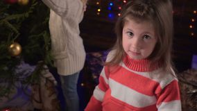 Two girls decorate a Christmas tree and talk stock video