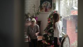 Two girls decorating Christmas tree in the home. The camera shoots from behind of the wall. Two Sisters decorate a Christmas tree. Girls gives each other five stock video footage