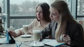 Two girls designers discuss the project using tablet in cafe stock video