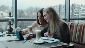 Two girls designers discuss the project using tablet in cafe stock footage