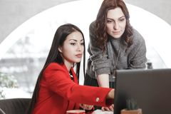 Two girls designers are working with laptop and documentation at the project in the stylish office. Project creation royalty free stock photo