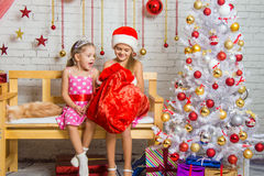 Two girls discover a bag of gifts Royalty Free Stock Photos