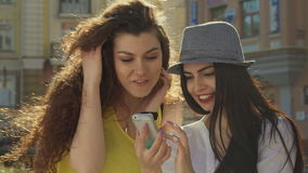Two girls discuss something on smartphone. Two attractive caucasian girls discussing somethng on smartphone. Female friends having fun on the street of the city stock footage