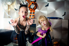 Two girls disguised as a tiger and as a witch are frightening someone in All Saints' Day. Halloween at home royalty free stock photography