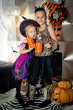 Two girls disguised as a tiger and as a witch are waiting for some candies in All Saints' Day. Two girls disguised as a tiger and as a witch are stock images
