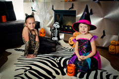 Two girls disguised as a tiger and as a witch are waiting for some candies in All Saints' Day. Halloween at home stock image