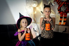 Two girls disguised as a tiger and as a witch are waiting for some candies in All Saints' Day. Halloween at home royalty free stock images