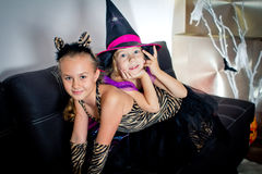 Two girls disguised as a tiger and as a witch are waiting for some candies in All Saints' Day. Halloween at home royalty free stock photos