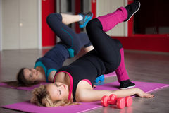 Two girls do aerobics exercises on mats in fitness center Stock Images