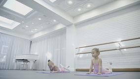 Two girls do arch laying on the mats while ballet class with famous trainer. Children stretch their heads to their feets in this position very diligently stock video