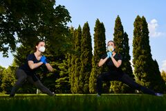 Two girls do sports exercises in protective masks in the open air in park. Social distancing. Alternative fitness COVID-19