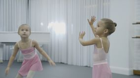Two girls do the trunk turnings with rasing hands during the ballet class. Little dancers in pink bresses and with buns stand in the big bright room and stock video footage