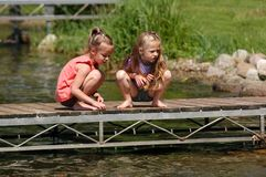 Two Girls On A Dock. Two girls sit out on a dock on a warm, sunny summer's morning watching the fish around the dock at their grandparents' cabin Stock Photography