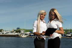 Two girls with the documents standing on the pier Stock Image