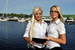 Two girls with the documents standing on the pier Stock Photo