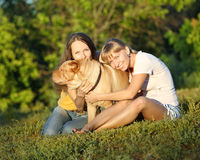 Two girls with dog. In summer stock image