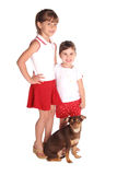 Two girls with dog isolated on white. Isolated on white these two young girls with their dog full view Stock Photo