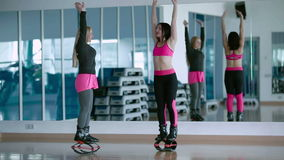 Two girls doing the breathing exercises in the kangoo shoes stock video footage