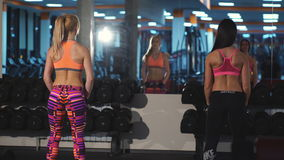 Two girls doing the breeding the hands apart with dumbbells. In the hall trengereid stock footage