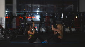 Two girls doing exercise on press. In gym stock video footage