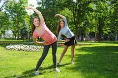 Two girls doing an exercise tilts aside outdoors Stock Images