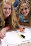 Two girls doing homework. Two teenage girls doing homework with paper, pencils, and with a cell phone close Royalty Free Stock Photo