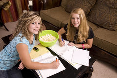 Two girls doing homework with popcorn. Two teenage girls doing home work with popcorn close at hand Stock Images