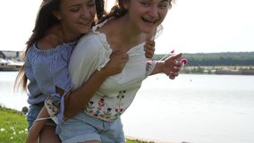 Two girls doing piggyback. Two girls doing piggyback, having fun laughing joyful and playful piggyback. Enjoying nature landscape on the lake stock footage