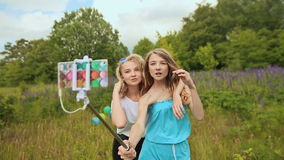 Two girls doing selfi with selfi stick. Two teen girls doing selfi with selfi stick stock video footage