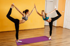 Two girls doing stretching exercises. In gym Stock Photos