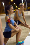 Two girls doing stretching at night. Stock Images