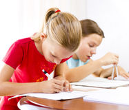 Two girls doing their homework stock images