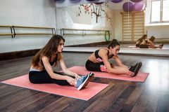 Two girls are doing yoga, aerobics, pilates exercises. In the gym stock image