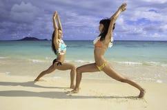 Two girls doing yoga at the beach. Two girls in bikinis and flower lei doing yoga at the beach in Lanikai, Hawaii Royalty Free Stock Image