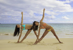 Two girls doing yoga at the beach. Two girls in bikinis and flower lei doing yoga at the beach in Lanikai, Hawaii Stock Photo