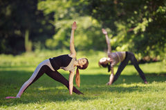 Two girls doing yoga exercises in park Stock Image