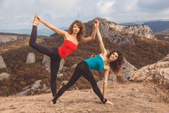 Two girls are doing yoga in mountains landscape Royalty Free Stock Photo