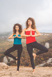 Two girls are doing yoga in mountains landscape Royalty Free Stock Images