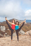 Two girls are doing yoga in mountains landscape Royalty Free Stock Photography