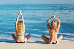Two Girls Doing Yoga Poses On The Shore Of The Caribbean Sea Stock Photos