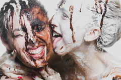 Two girls doused with white and dark chocolate. passionate women Royalty Free Stock Images