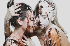 Two girls doused with white and dark chocolate. passionate women Stock Photo