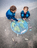 Two girls drawing Earth with chalks Royalty Free Stock Photos